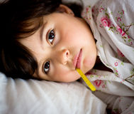 Little girl with thermometer in bed Stock Photos