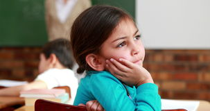 Little girl thinking hard during class. In elementary school stock footage