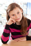 Girl thinking while sitting at a desk Royalty Free Stock Photo