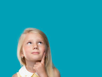 The little girl is thinking. About something on a blue background Stock Photos