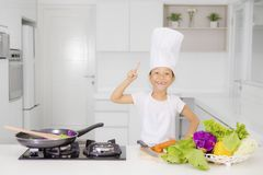 Little girl thinking something in the kitchen. Picture of little girl is thinking something while preparing healthy meal and standing in the kitchen Stock Photography
