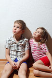 Little girl and thoughtful boy sitting stock images