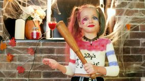 Little girl threatens with baseball bat, harly quinn character, dangerous child, halloween party stock video footage