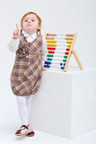 Little girl threatens finger next to colorful abacus Royalty Free Stock Photo