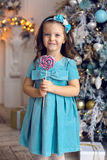 Little girl three years in a blue dress licks Royalty Free Stock Photos