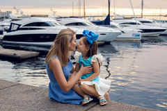 Little girl three years sitting on the lap of the mother with long blond hair Stock Images