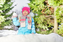 Little girl throw snowball hiding behind snow wall Royalty Free Stock Photo