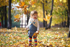 Little girl throwing autumn leaves in the air Stock Photo
