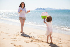 Little girl throwing beach ball Stock Photo