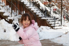 Little Girl Throwing a Giant Snow Ball. Winter portrait of a smiling little girl playing in the snow throwing a big snow ball Stock Photo