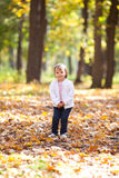 Little girl throwing leaves  in the forest Stock Photo