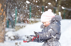 Little girl is throwing snow Stock Image
