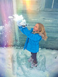 Little girl throwing snow in rainbow Royalty Free Stock Images