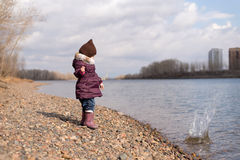 Little girl throwing a stone into river Stock Images