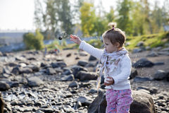 Little girl throwing the stones Royalty Free Stock Image