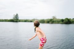 Little girl throwing stones in water at the beach Royalty Free Stock Image