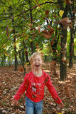 Little girl throwing up dried leaves Royalty Free Stock Image