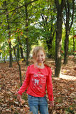 Little girl throwing up dried leaves Stock Photography