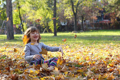 Little girl throws autumn leaves Royalty Free Stock Images