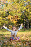 Little girl throws autumn leaves Stock Images