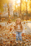 Little girl throws fallen leaves. Autumn. Royalty Free Stock Photos