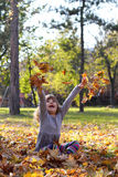 Little girl throws leaves Royalty Free Stock Images