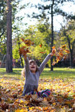 Little girl throws leaves in autumn park Stock Image