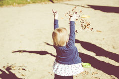 Little Girl Throws Leaves Stock Photography