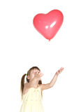 Little girl throws up red balloon Royalty Free Stock Photos