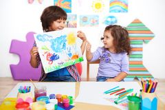 Little girl with thumb up looking at drawing of Royalty Free Stock Photography