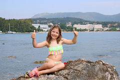 Little girl with thumbs up on summer vacation Stock Images