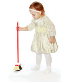 Little girl tidying sweeping the floor Stock Photo
