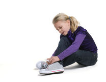 Little girl tie on her shoes. Beautiful little girl tie on her sportsmanlike  shoes Stock Photography