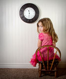 Little girl in time out or in trouble looking. With clock on the wall Stock Photo