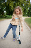 Little girl to stand leaning on a wheel of the scooter. Royalty Free Stock Photo
