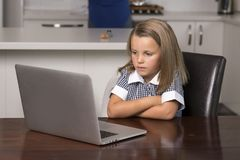 Little girl 6 to 8 years old sitting at home kitchen enjoying with laptop computer concentrated watching internet cartoon movie royalty free stock photography