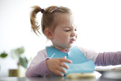 Little girl toddler picking her food, making faces. Childhood problems, picky eater, eating habits, terrible two concept stock photo