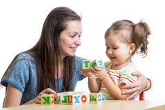 Little girl together with mother playing cubes Stock Image