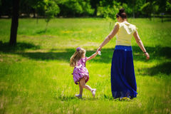 Little girl together with mother run and play on a grass in the Stock Photo
