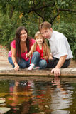 Little girl together with parents sits on the bank Stock Image