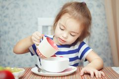Little girl carefully pours milk from cup to bowl Stock Photography