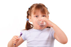 Little girl with tooth brush drinks water Royalty Free Stock Photo