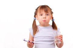 Little girl with tooth brush and glass with water Royalty Free Stock Photo