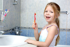Little girl with toothbrush Stock Images