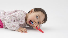 Little girl with toothbrush in her hand on white background Royalty Free Stock Photo