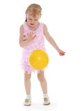Little girl tosses the ball Stock Images
