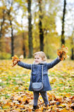 Little girl tossing leaves in autumn park Stock Photography