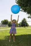 Little Girl Tossing Up Ball Stock Photography
