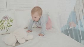 Little girl touch the bear near the bed. Slow Motion. Baby milestone, toddler, 1 year old. Happy childhood.  stock video footage