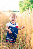A little girl touches the hand ears of wheat in a field in summer Stock Photos